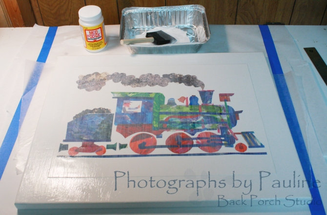 Using a sponge brush, I applied a thin coat of Mod Podge to the canvas and print from top to bottom.